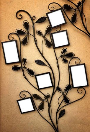 wall decor: Curly iron picture holder with 6 empty frames leaning on a yellow wall