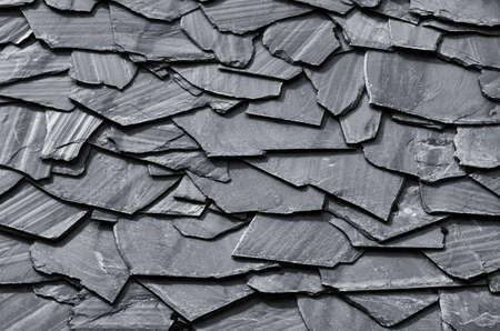 dark grey slate: Rustic background of decorative black schist blades