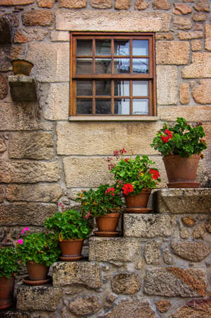 decorative balconies: Rural house facades decorated with old vases of flowers