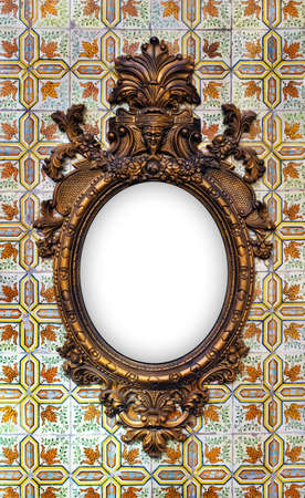 tiled wall: beautiful and complex brass baroque frame hanged on a tiled wall