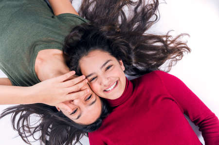 bff: Two joyful teenager girl friends laying on the floor with their heads together