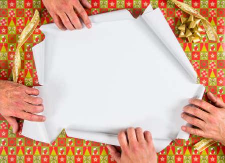 Kerstmis verpakt geopend aanwezig opgelicht door vier handen Stockfoto