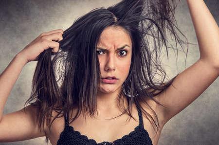 enojo: Chica adolescente Morena con la expresión de la ira a arrancarse el pelo desordenado