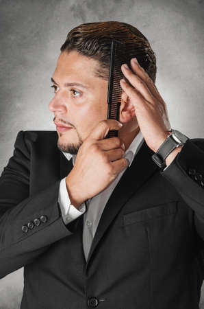 stylish men: Elegant man in dark suit combing his hair