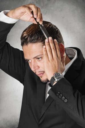 slick: Elegant man in dark suit combing his hair