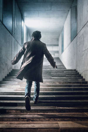 Man with a handgun running up a stairway in a modern building