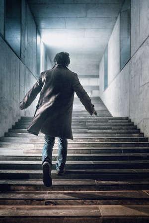 Man with a handgun running up a stairway in a modern building
