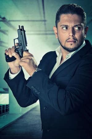 undercover agent: Male agent in an alert position and loading the chamber of his handgun