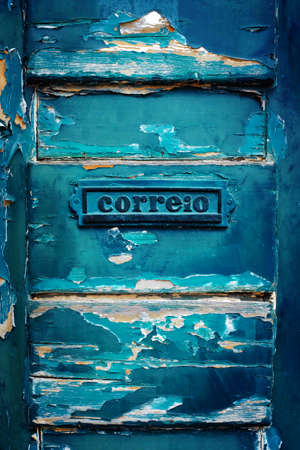 Closeup on a mailbox in an old wooden door with peeling blue paint Stock Photo