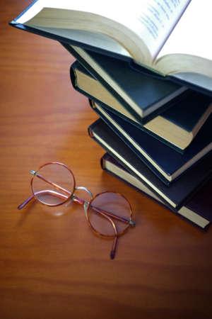 apilar: Pila de libros viejos y un par de vidrios de la vendimia en la parte superior de una mesa Foto de archivo