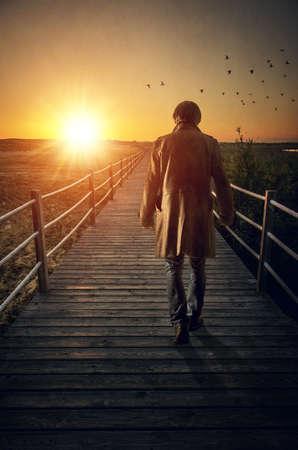 A man with long coat walking in a boardwalk into de sunset