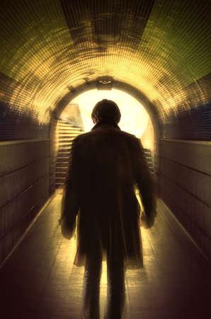 Man met een lange jas weg in een wandelen onder doorgang naar het licht Stockfoto