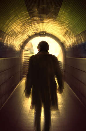 Man with a long coat walking away in a under passage to the light