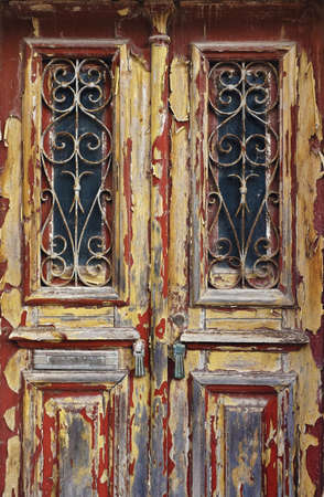 wood door: Closeup on an old and neglected wooden door with ironwork windows