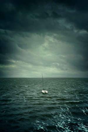 Little Sailing Boat Adrift In Troubled Waters And Under A Stormy Sky Stock Photo