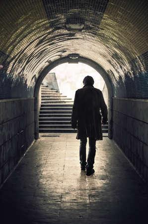 detras de: Vista posterior de un misterioso hombre que camina en un túnel padestrian Foto de archivo