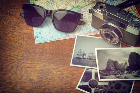 Vintage camera, map, sunglasses and photo prints on wooden table with copy space Stock Photo