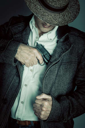holster: A gangster with a hat drawing his handgun from the holster Stock Photo