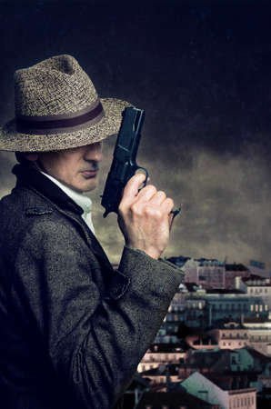 spy: A gangster with hat holding a handgun with a city in the background
