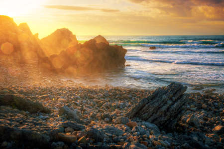 sea wave: Seascape with sun beams at sunset in Abano Beach, Portugal.
