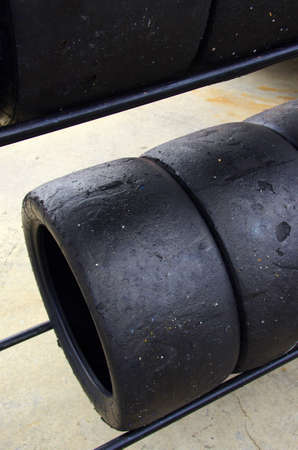 slick: Rows of worn out slick tires in a pit box of a racing circuit