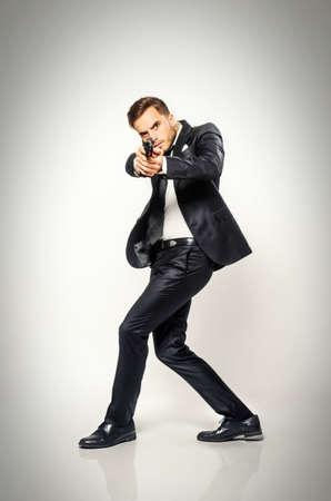 pistolas: Agente secreto en traje negro girando rápido y objetivo de una pistola Foto de archivo