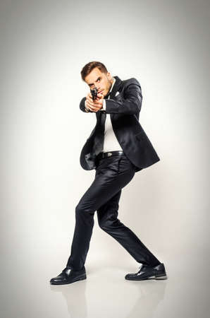 Secret agent in black suit turning fast and aiming a handgun