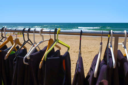 hangers: Row of surfing wet suits on hangers drying under the sun at the beach