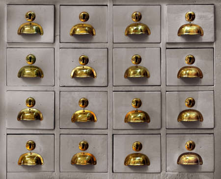 old furniture: Rows of little drawers with golden handles in an old furniture module