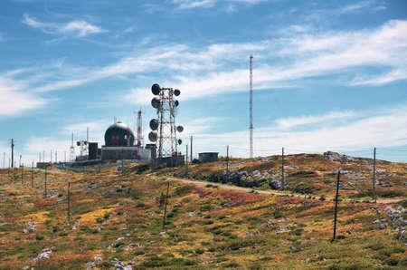 comunicación: antenas de comunicaciones inalámbricas grandes en una colina bajo un cielo azul Foto de archivo