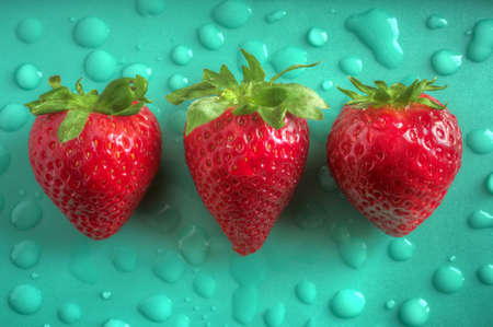 aligned: Three aligned strawberries over emerald green background with water drops Stock Photo