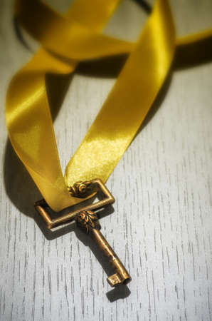 skeleton key: Old skeleton key with yellow thick ribbon over white wooden surface
