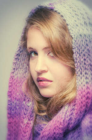 profile face: Studio portrait of a pretty blond teenager girl wearing a wool scarf in her head