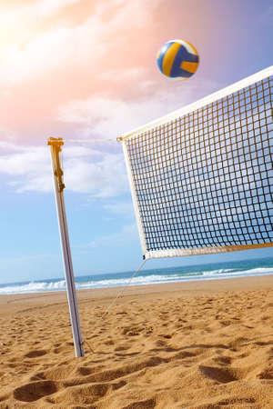 Helle Strandszene mit einem Netz und Volleyball bei Sonnenuntergang
