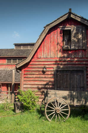 barns: Red wooden western barn with a old wagon in foreground