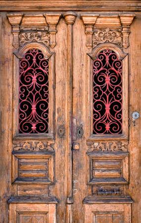 ironwork: Double wooden door detail with red decorative ironwork in windows