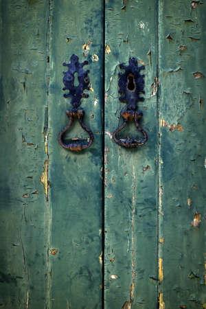 green door: Two black door handles in old green wooden doors