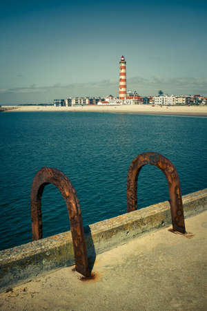 Pier with a pair of rusty handrails of a ladder with lighthouse in the background Stock Photo