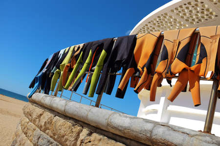 Row of hanging surfing wet suits drying under the sun at the beach Stock Photo