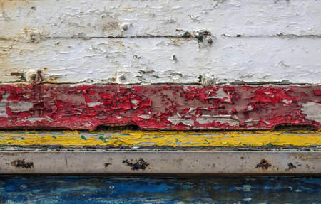 ship wreck: Background detail of old boat with red, yellow, blue and white peeling paint Stock Photo