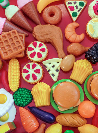 Collection of several pieces of plastic toy food over red background