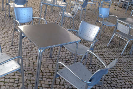 shinning light: Empty modern silver chairs and tables in a terrace