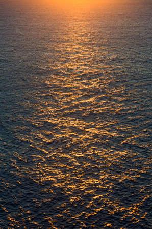 Bird view of warm sunset light over the vast rippling ocean