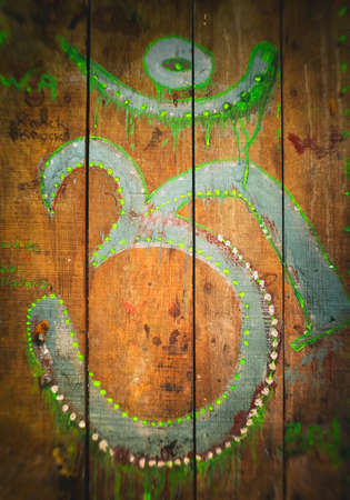 aum: Om sign roughly painted green on an old wooden surface Stock Photo