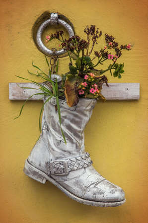 ahorcada: Bota vieja pintada de blanco con flores colgadas en una pared amarilla Foto de archivo