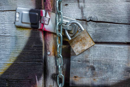 Wooden gate covered with gray paint and colorful graffity and padlock
