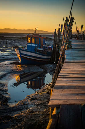 Sunset view of Carrasqueira palaffitic port with old boats in Portugal