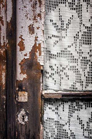 Detail of old window frame with knitting needlework curtain