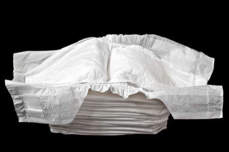 A Stack of White Disposable Diapers Isolated on a Black Background