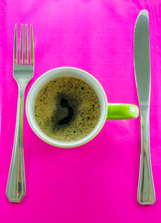 Green mug with coffee erroneously with cutlery on pink background